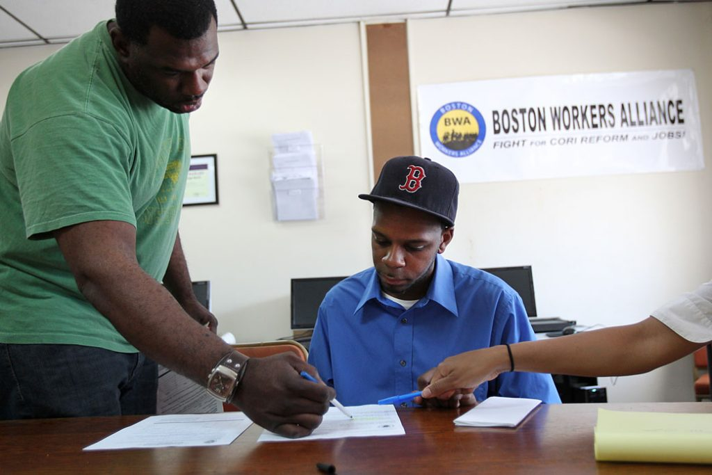A staffer at a Boston Workers Alliance office shows a job applicant how he can apply to get his criminal record sealed, June 2011