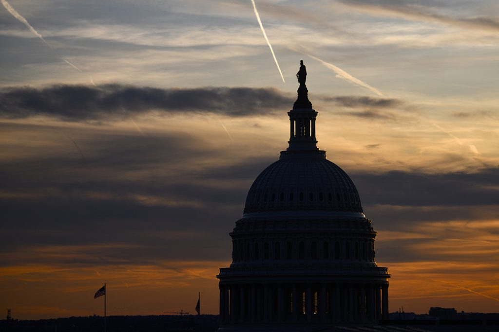 Streaks in the sky form at sunset behind the U.S. Capitol Building on November 13, 2019, in Washington, D.C.