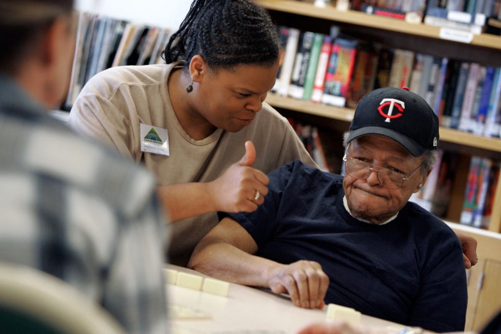 An employee at a Minneapolis nursing home sits at a table with a group of residents playing dominoes, January 2006.
