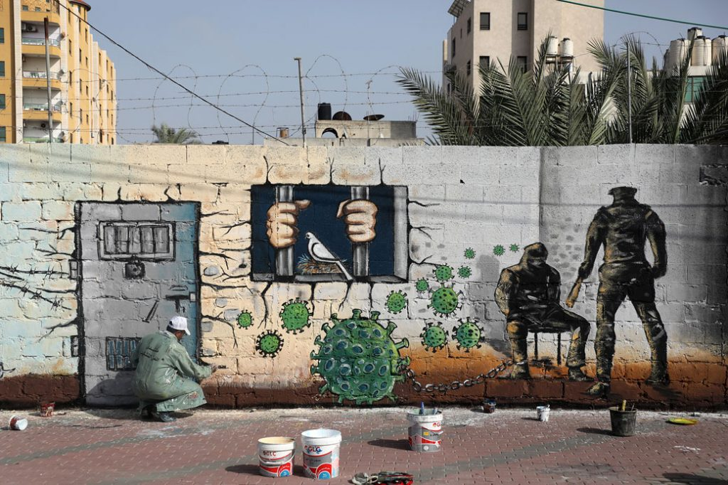 An artist paints a mural in Gaza City on April 20, 2020.