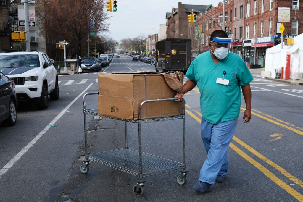 A medical worker walks outside of a special COVID-19 intake area at Maimonides Medical Center in New York City, April 2020.