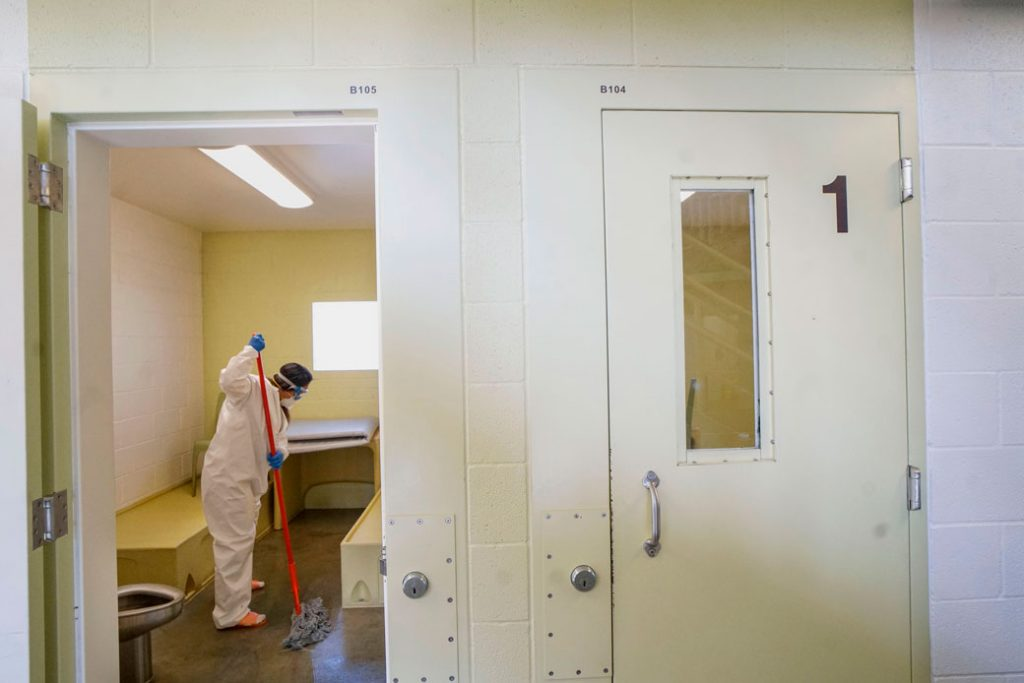 An inmate cleans a jail cell at a women's detention facility in Santee, California, on April 22, 2020.