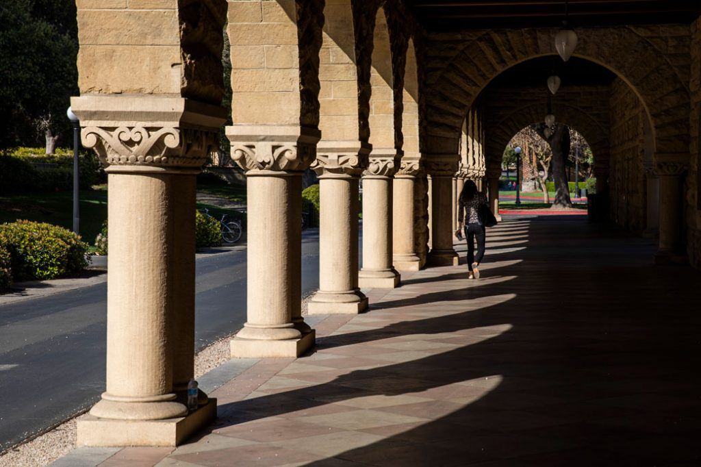 A person walks past archways during a quiet morning at Stanford University on March 9, 2020, in Stanford, California.