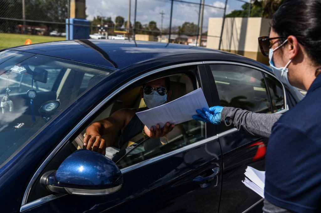 A man collects unemployment forms at a drive-through collection point in Hialeah, Florida, on April 8, 2020.
