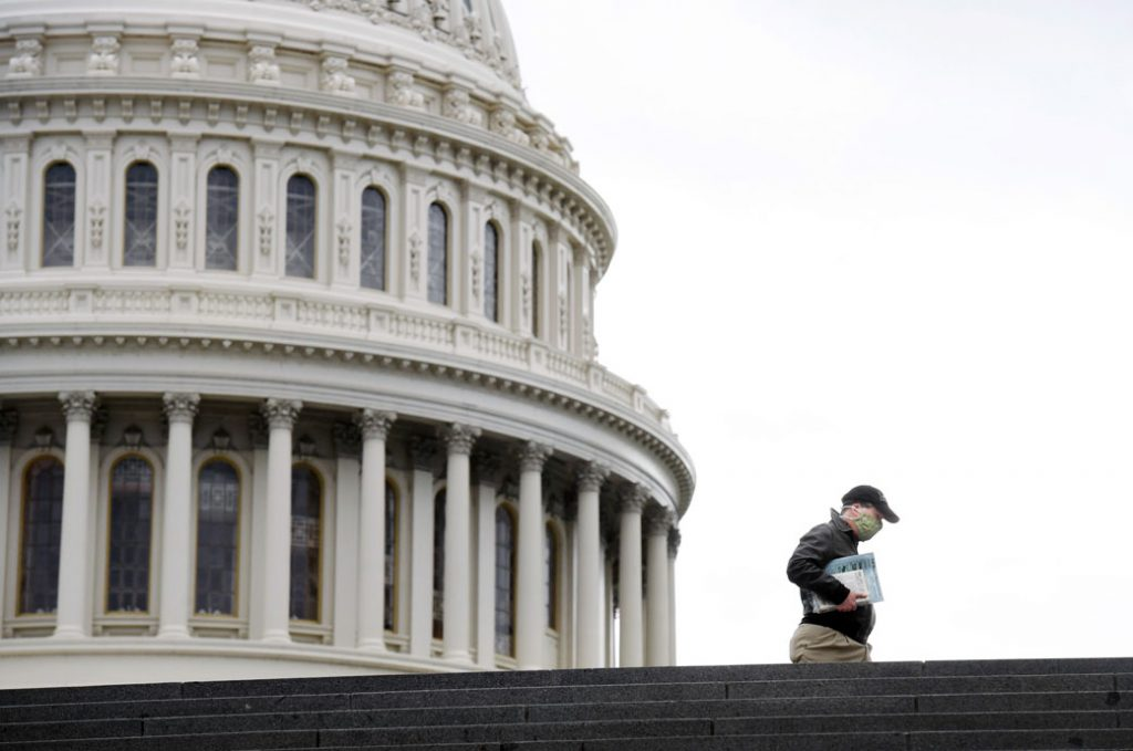 A pedestrian wears a mask while walking near the U.S. Capitol, April 2020.