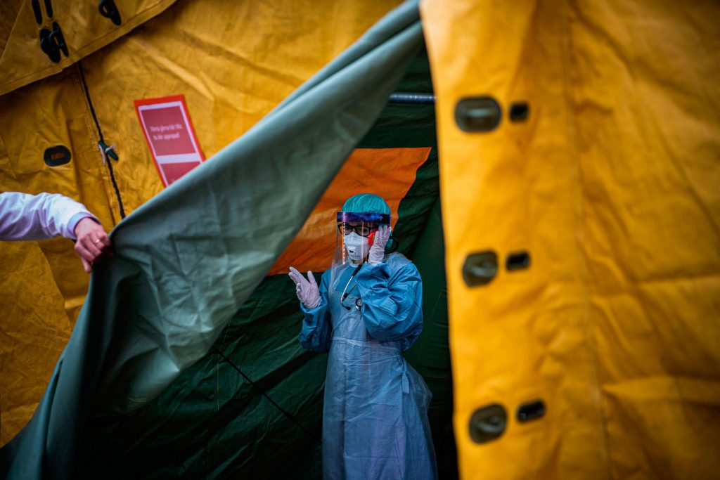 A medical staffer at Sophiahemmet hospital in Stockholm talks on a cell phone while exiting a tent for testing and receiving potential COVID-19 patients, April 2020.