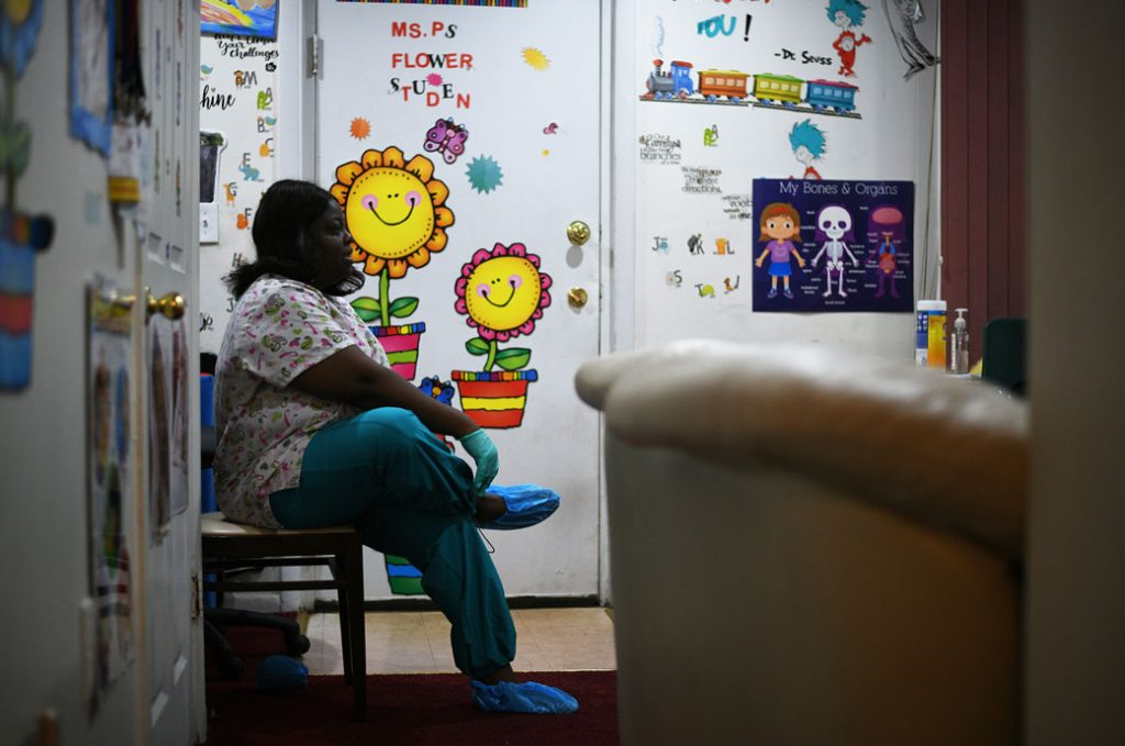 Angelique Speight-Marshall puts on protective gloves and slippers to protect her clients from the coronavirus inside her child care facility, March 2020.
