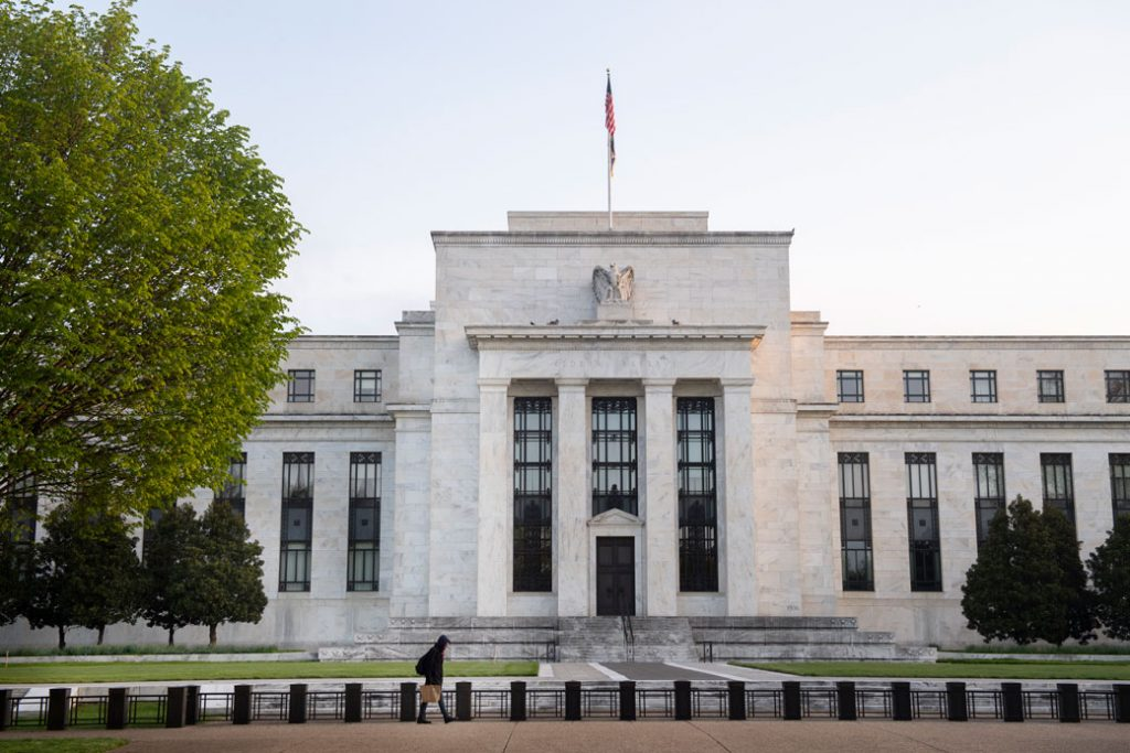 A person walks by the Federal Reserve building in Washington, D.C., on April 25, 2020.