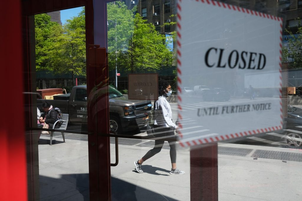 People walk through a shuttered business district in New York on May 12, 2020.