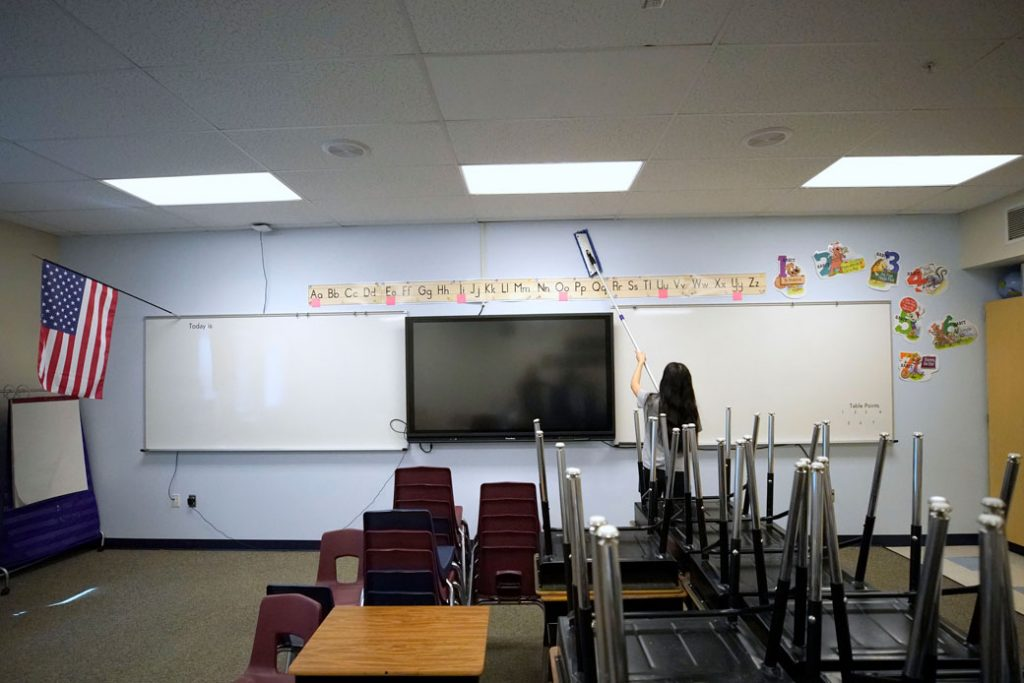A worker cleans the walls in a classroom at a school in Provo, Utah, on May 18, 2020.