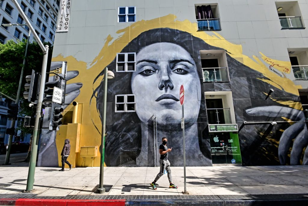 A man wearing a face mask walks past a mural of a woman on a street that is otherwise empty due to shelter-in-place orders in response to the COVID-19 outbreak in Los Angeles, March 2020.