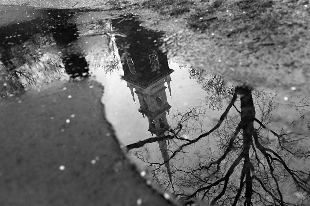 A building on a university campus in Massachusetts is seen reflected in a puddle on April 27, 2020.