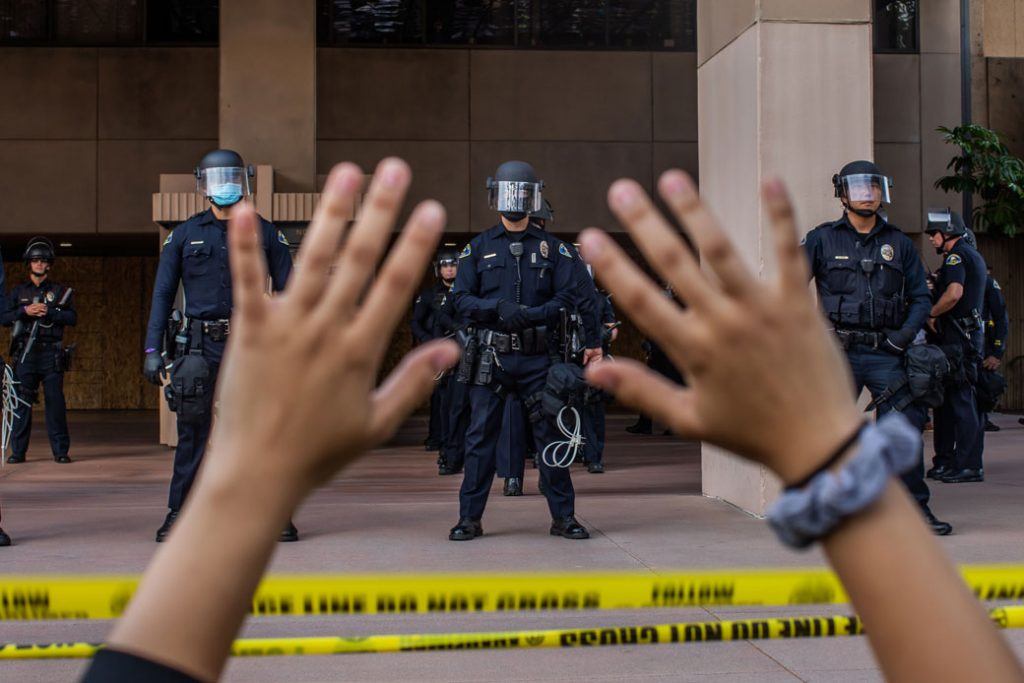 A demonstrator holds her hands up in front of police officers at Anaheim City Hall on June 1, 2020, in Anaheim, California, during a peaceful protest over the death of George Floyd.