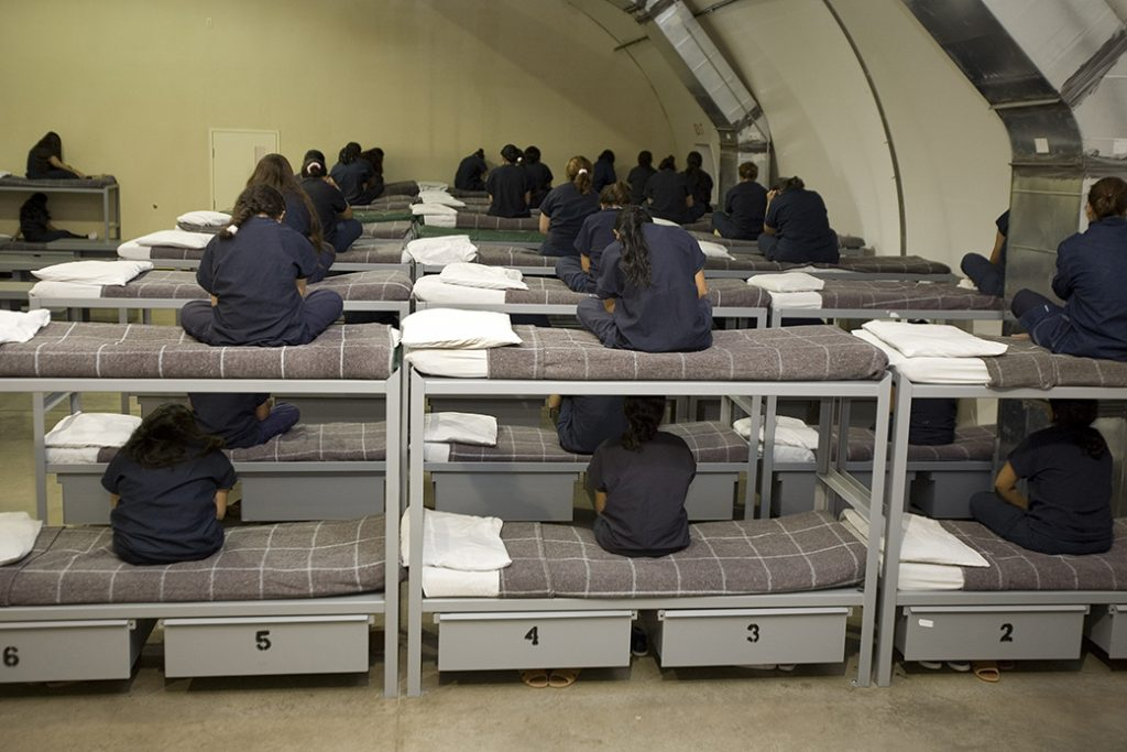 Female detainees turn their backs to the visiting media, as instructed by Homeland Security officials, inside a Homeland Security immigration detention center in Texas, 2007.