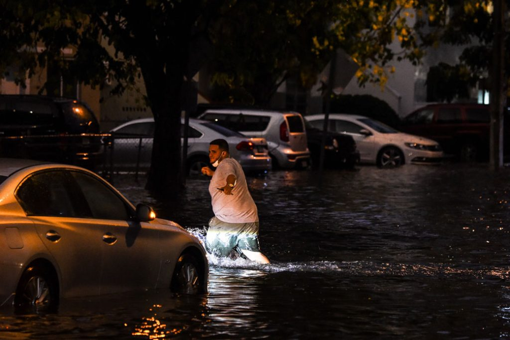 A man walks through floodwaters during heavy rainfall in Miami on May 26, 2020.