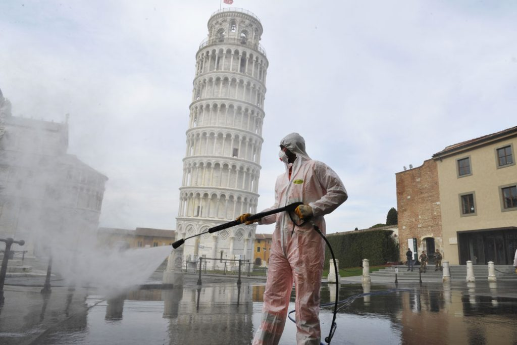 A worker carries out sanitation operations in a deserted Piazza dei Miracoli in Pisa, Italy, on March 17, 2020.