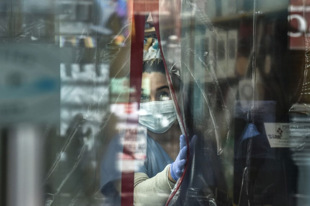 A pharmacist wearing personal protective equipment works in the Elmhurst neighborhood of New York City in April 2020.