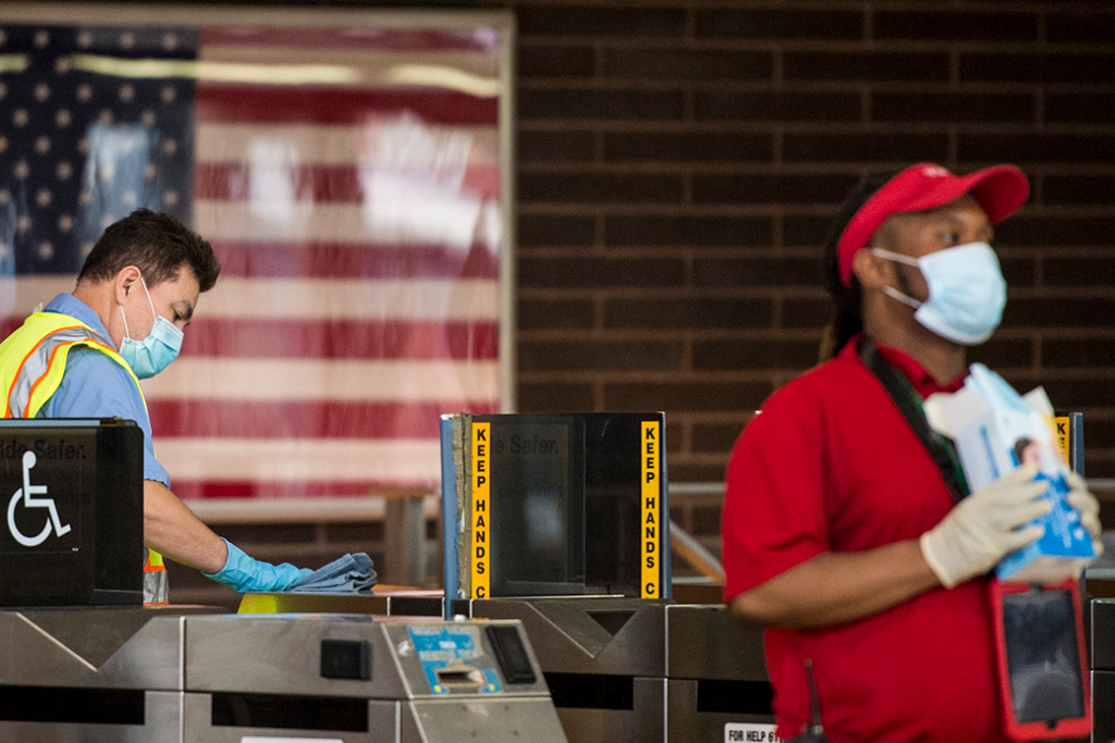 One transit employee wipes down the turnstiles while another passes out masks in the Ashmont Red Line station in Boston, June 2020.