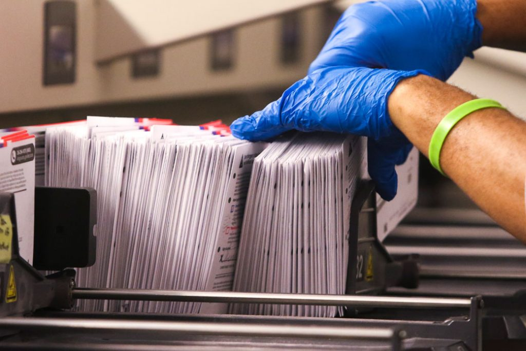 An election worker handles vote-by-mail ballots in Renton, Washington, on March 10, 2020.