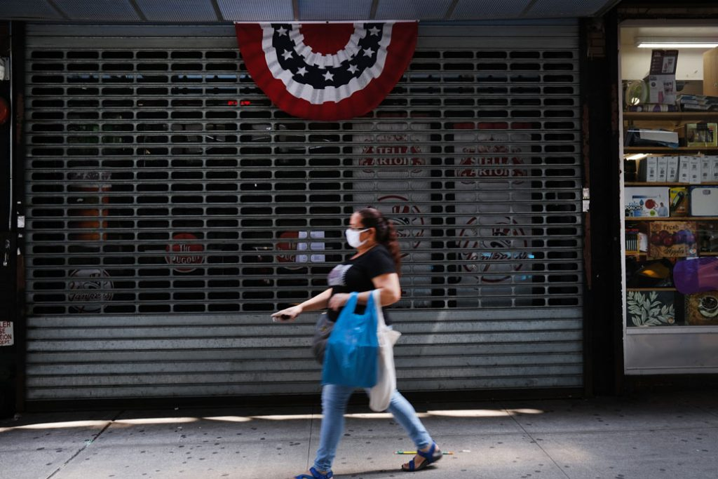 A woman walks by stores, many closed, in the Bronx in New York City on July 23, 2020.