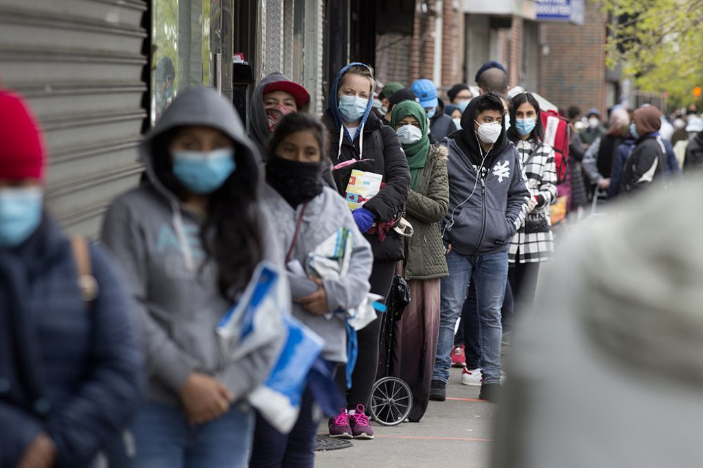 People wearing protective masks form a line to receive free food from a food pantry, May 2020 in Brooklyn, New York.