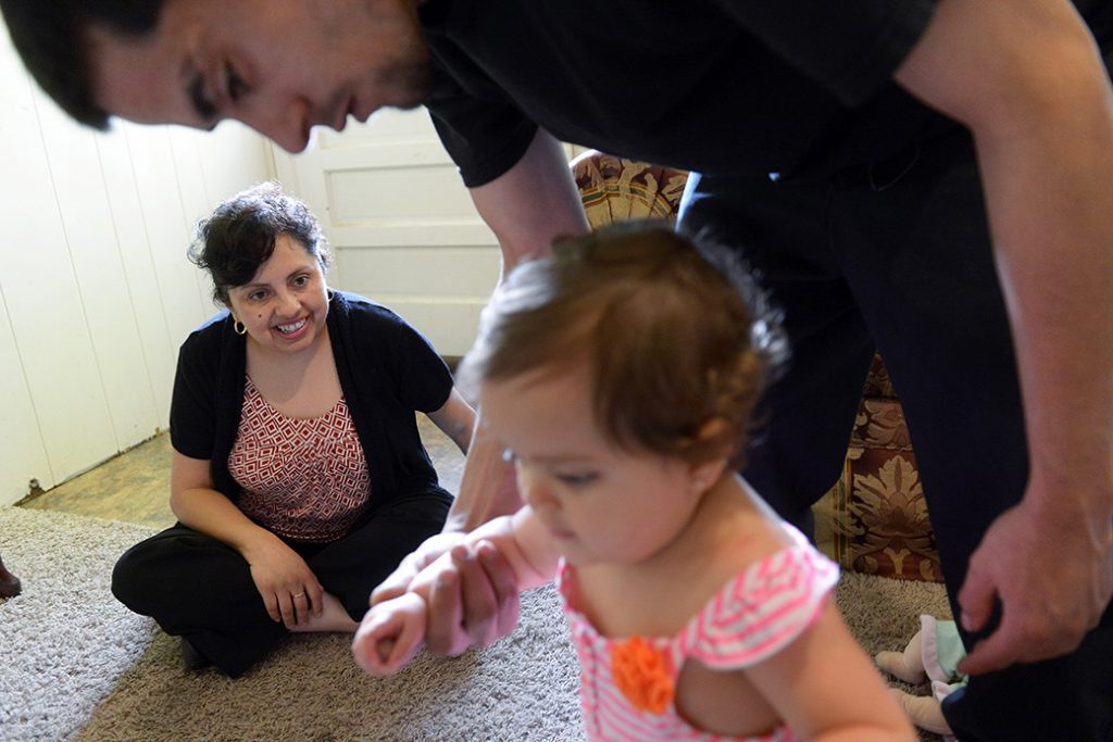 A father helps his 1-year-old daughter walk as a family support worker visits the family's home, May 2013, in Virginia.