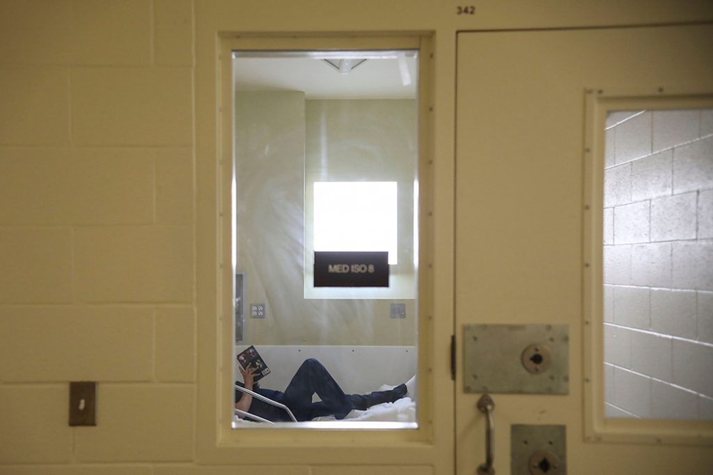 An inmate reads a book while in the infirmary at a detention facility in California, April 2020.