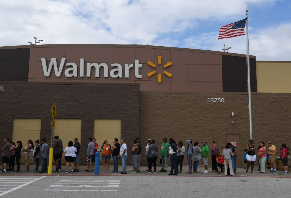 People wait in line for a Walmart store to open after Hurricane Harvey caused heavy flooding in Houston, Texas on August 30, 2017. Monster storm Harvey made landfall again Wednesday in Louisiana, evoking painful memories of Hurricane Katrina's deadly strike 12 years ago, as time was running out in Texas to find survivors in the raging floodwaters. / AFP PHOTO / MARK RALSTON        (Photo credit should read MARK RALSTON/AFP via Getty Images)