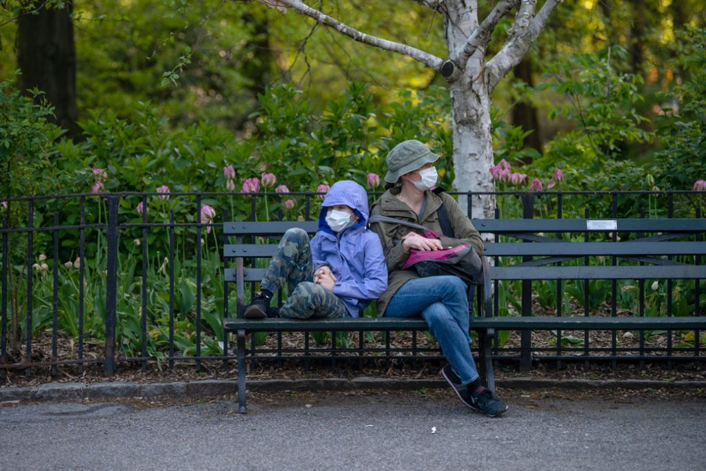 A mother and child sit on a bench in Central Park amid the COVID-19 pandemic, New York, May 2020.