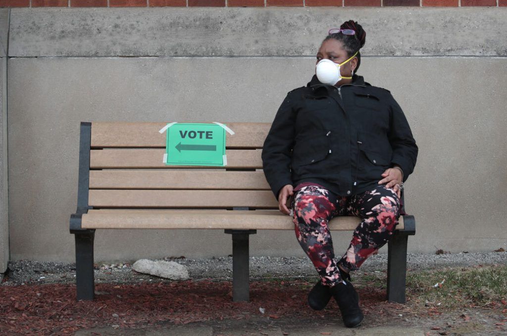 A woman rests after voting, April 2020.