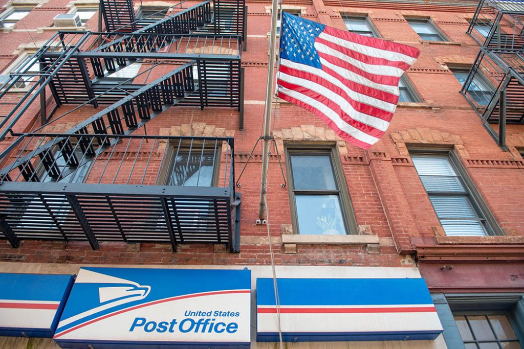 An American flag waves outside a post office, August 2020.