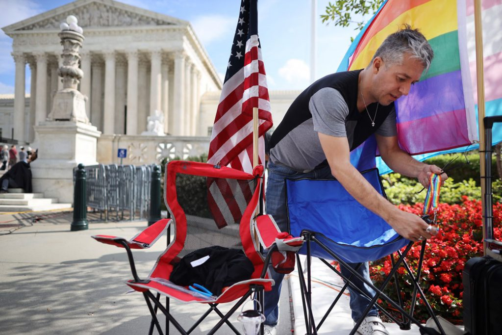 A man attaches a safety whistle to his chair while waiting in line outside the U.S. Supreme Court building for a chance to attend the Bostock v. Clayton arguments, October 2019.