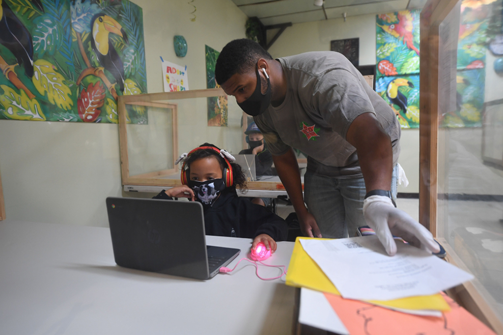 At a learning center in Culver City, Calilfornia, an instructor helps a student with her lesson at a desk separated from others by plastic barriers, September 2020.