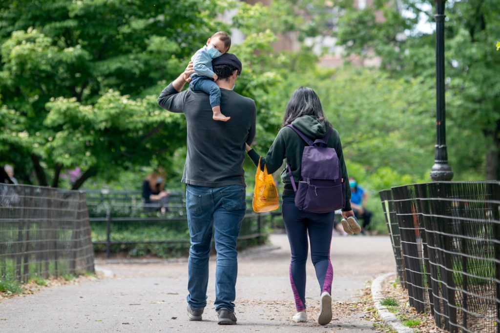 A young child wearing a mask sits on his father's shoulder in Central Park, New York, on May 24, 2020.