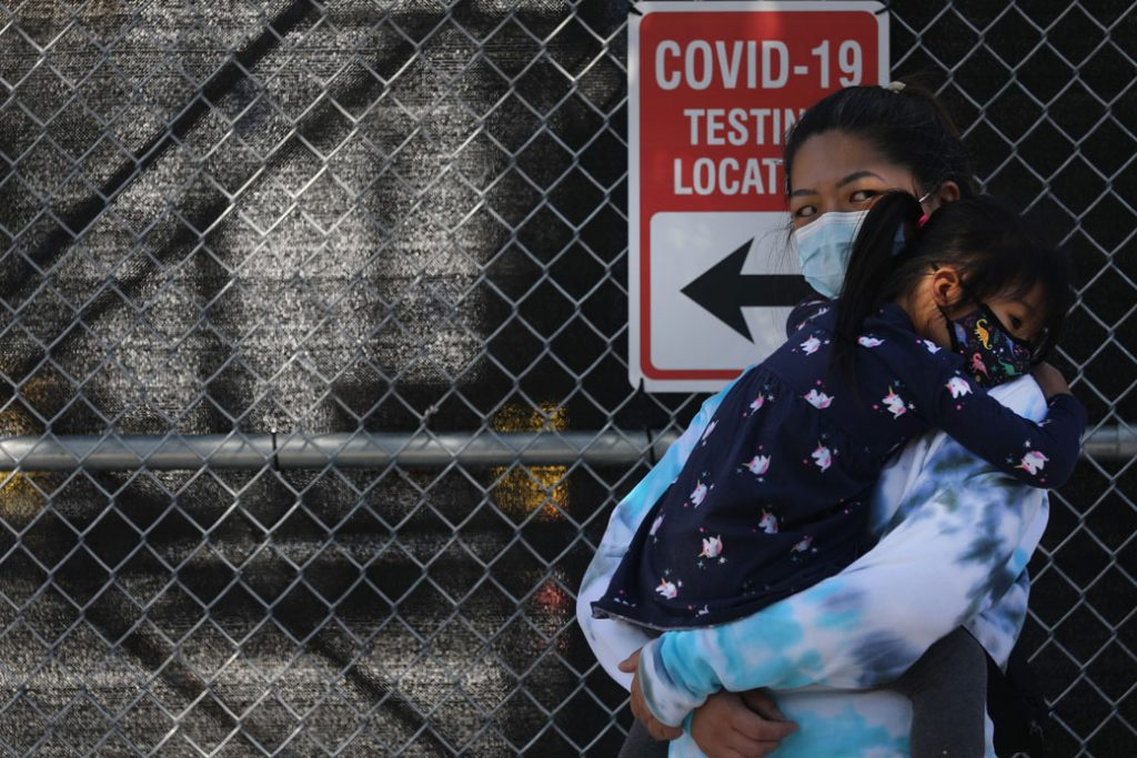 A mother and daughter wait in line to be tested for COVID-19 at a city test site in Brooklyn, New York, October 2020.
