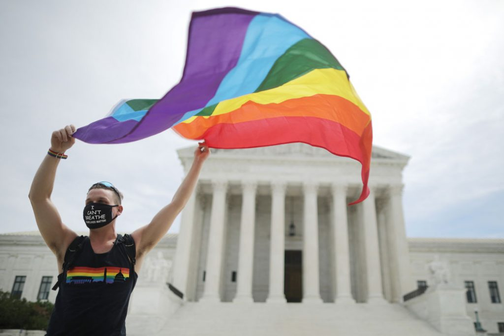 An advocate for LGBTQ rights holds a pride flag in front of the U.S. Supreme Court building in Washington, D.C., June 2020.