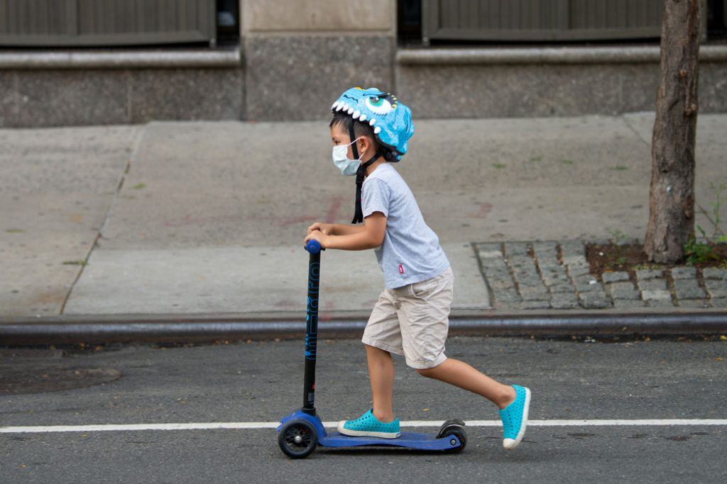 A child wearing a mask rides a scooter down the street in New York City, July 2020.