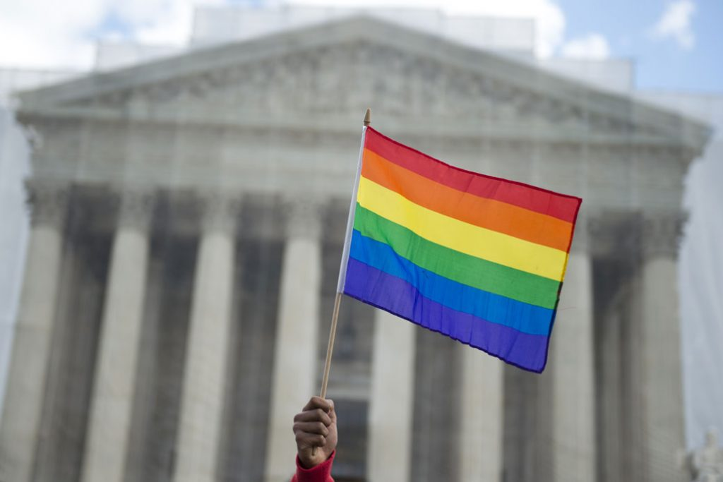 A pride flag is waved in front of the U.S. Supreme Court on March 26, 2013, in Washington, D.C.