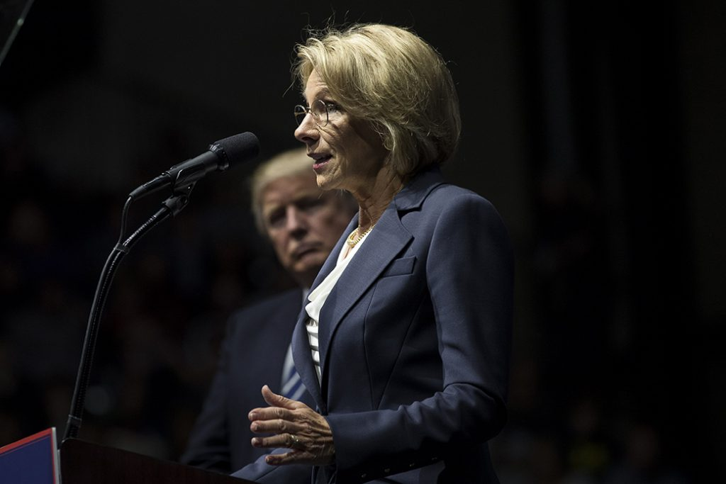 Then-President-elect Donald Trump looks on as Betsy DeVos, now his secretary of education, speaks at an arena, December 2016, in Grand Rapids, Michigan.
