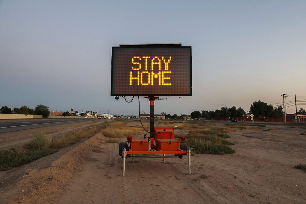 """A message is posted reading """"Stay Home"""" in a county hard hit by COVID-19."""