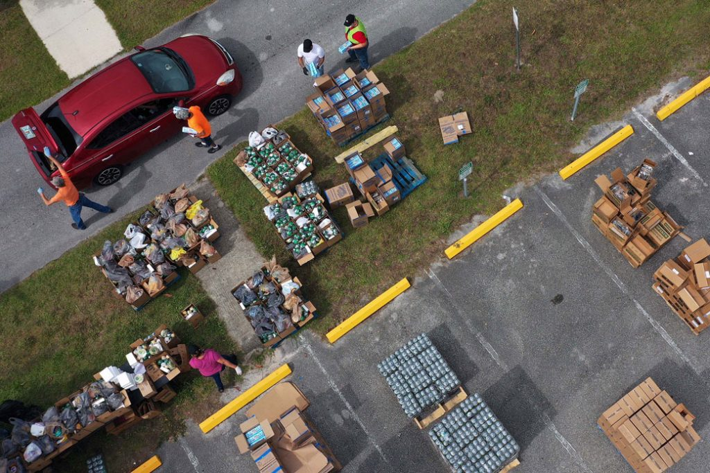 Volunteers distribute food from the Second Harvest Food Bank of Central Florida to families during a drive-through event on April 17, 2020, at the New Jerusalem Church in Kissimmee, Florida.