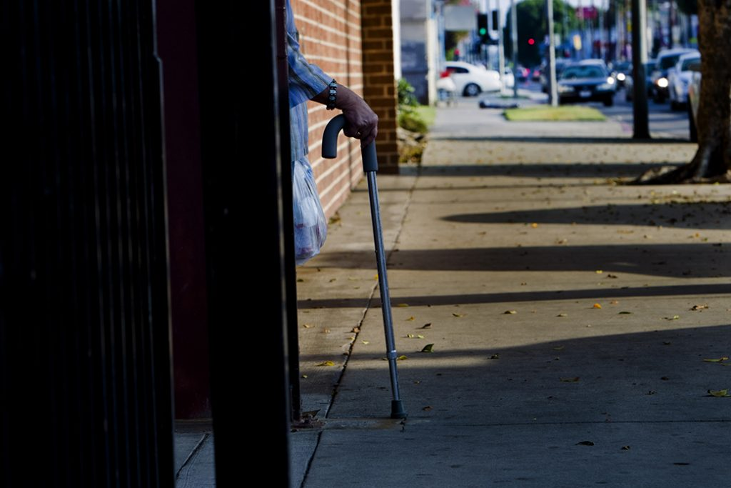 Holding onto her cane, a patient waits for a ride after a doctor's appointment in Los Angeles.