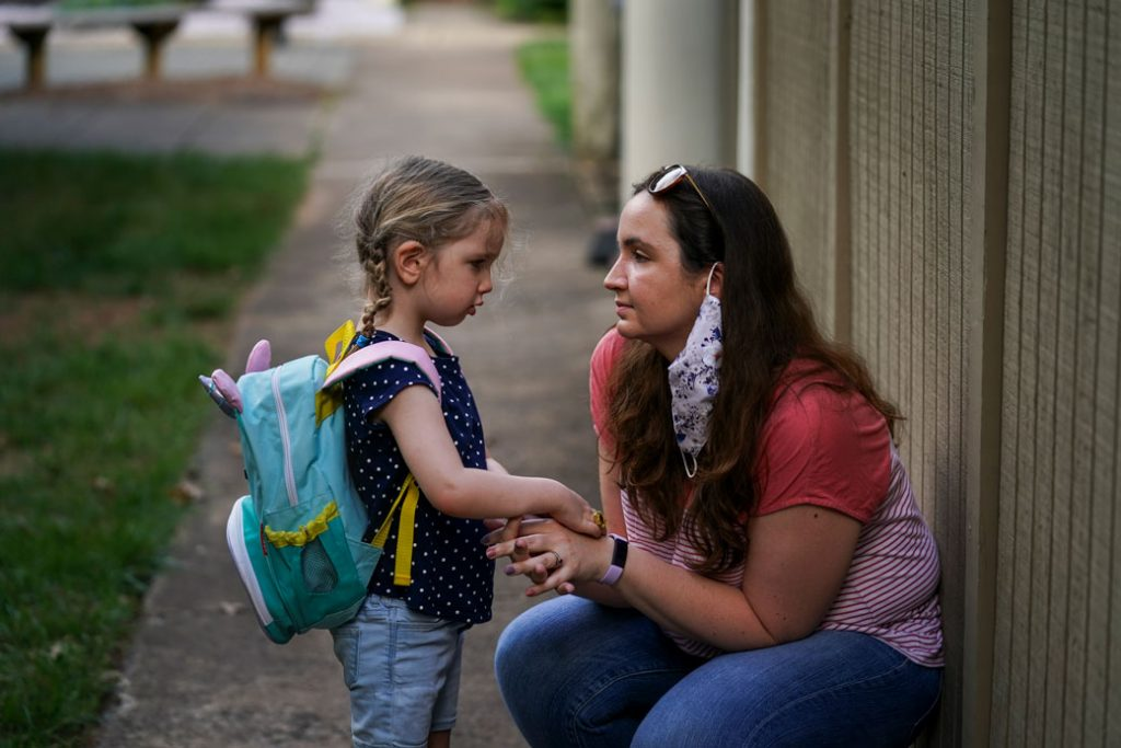 A woman consoles her daughter on her way to daycare, Reston, Virginia, August 2020.