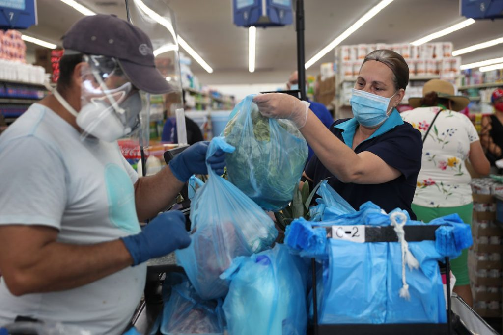 A woman stands behind a partial protective plastic screen and wears a mask and gloves as she works as a cashier at a supermarket on April 13, 2020, in Miami.