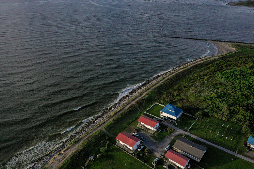 Homes sit next to the Gulf of Mexico in Grand Isle, the only inhabited barrier Island in Louisiana, which is threatened by a combination of sea level rise and sinking land due to climate change, August 2019.