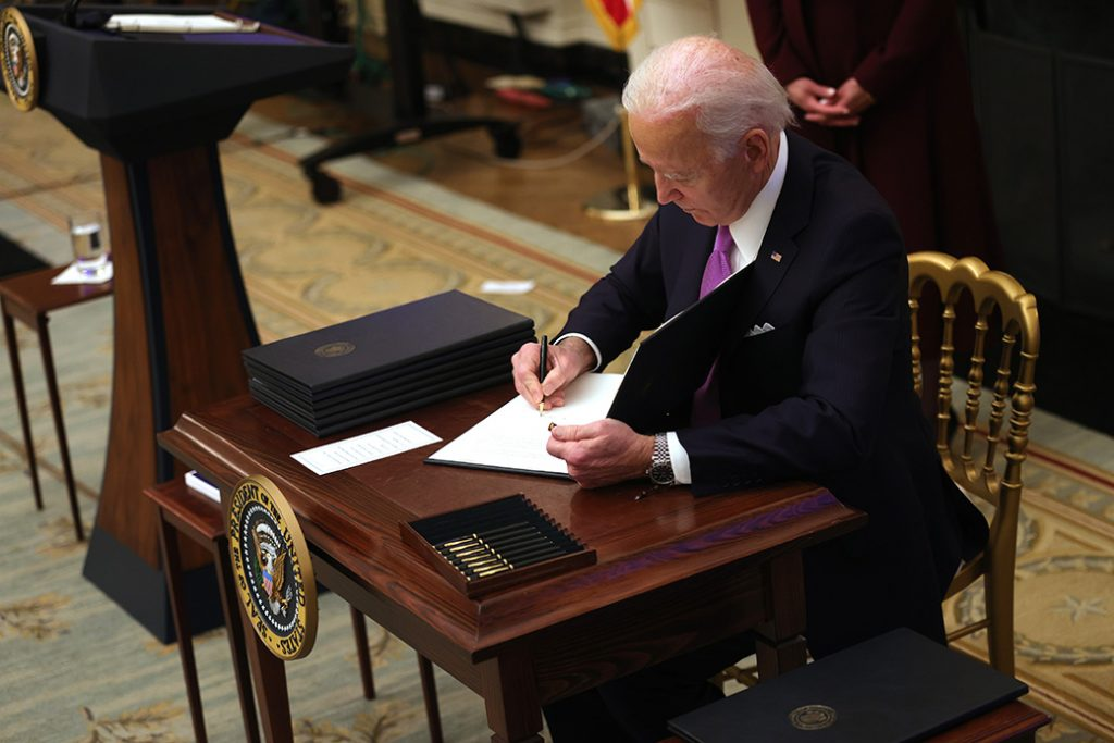President Joe Biden signs an executive order during an event in the State Dining Room of the White House, January 21, 2021, in Washington. President Biden delivered remarks on his administration's COVID-19 response and signed executive orders and other presidential actions.