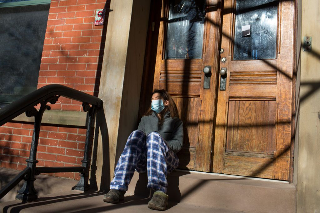 A COVID-19 patient, trying to recover at home, grabs fresh air on the front stoop of her home in Brooklyn, New York, on November 20, 2020.
