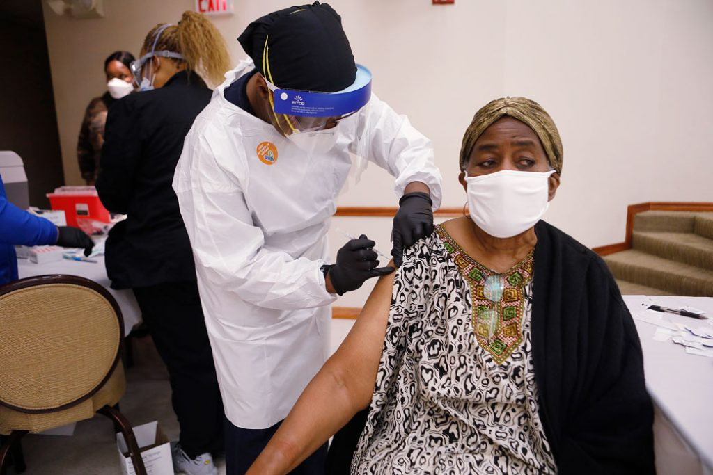 A health care worker administers the COVID-19 vaccine to a resident living in Tampa, Florida, on January 10, 2021.