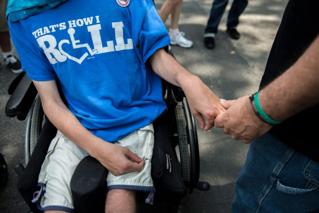 A father holds his son's hand during the first annual Disability Pride Parade in New York City on July 12, 2015.