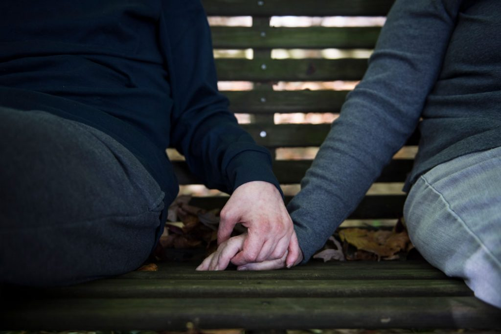 Barbara Altman holds hands with her son Andrew, who has microcephaly, on a bench at their home in Rockville, Maryland, on October 29, 2016.